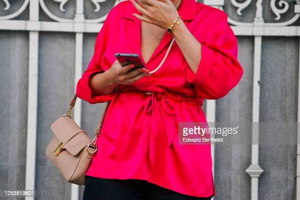 A passerby wears a neon pink jacket a salmonpink bag a golden small watch on June 28 2020 in Paris France