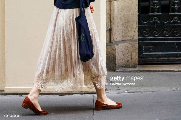 Passerby wears a pale pink pleated skirt with embroidery, brown flat shoes, a blue bag, on June 20, 2020 in Paris, France.