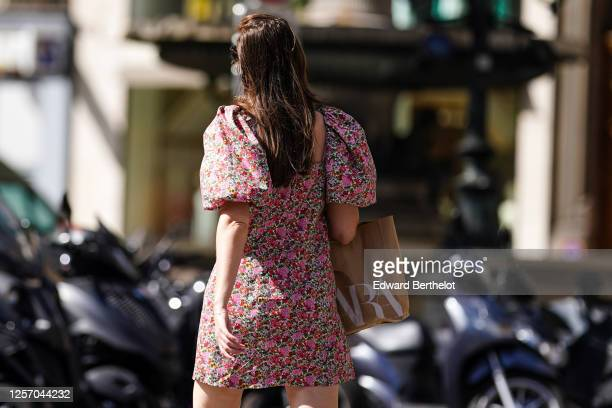 Passerby wears a pink floral print dress with puff shoulders, a Zara shopping bag, on July 09, 2020 in Paris, France.