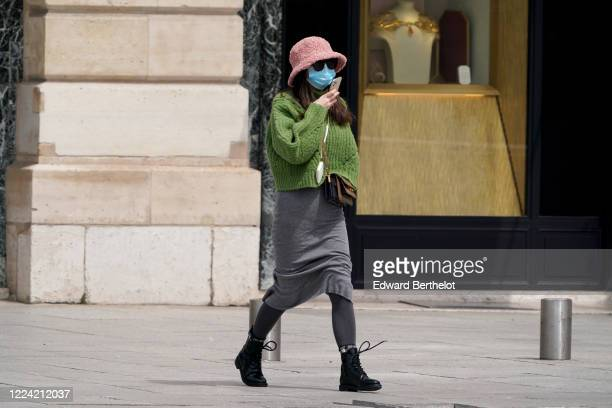 Passerby wears a pink fluffy wool hat, a green knitted wool pullover, a gray skirt, leggings, black shoes, in the streets of Paris, on May 11, 2020...