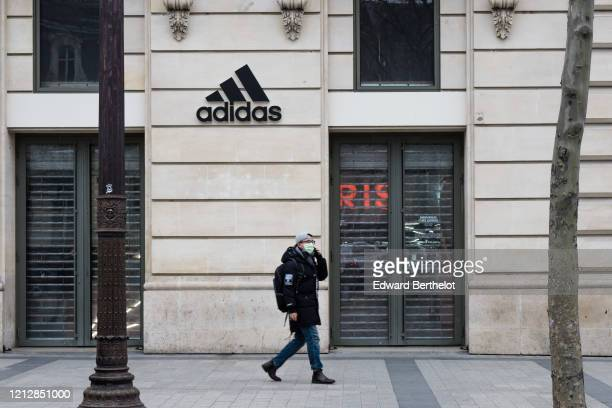Passerby wears a protective face mask, in front of a closed Adidas store, at Avenue des Champs Elysees, in the 8th quarter of Paris, as the city...