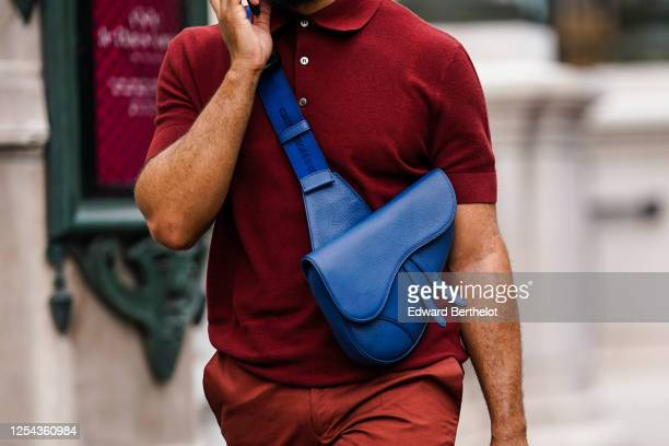 Passerby wears a red / burgundy polo shirt, a blue crossbody leather Dior Saddle bag, on July 04, 2020 in Paris, France.