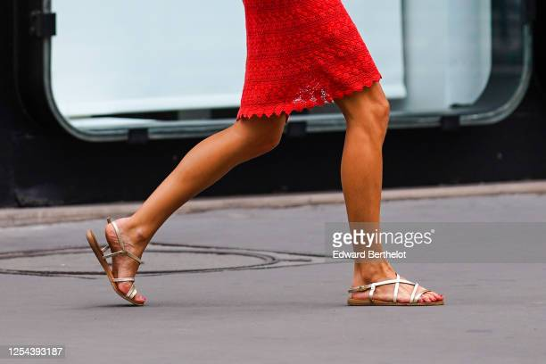 Passerby wears a red mesh dress with embroidery, golden gladiator flat sandals, on July 04, 2020 in Paris, France.