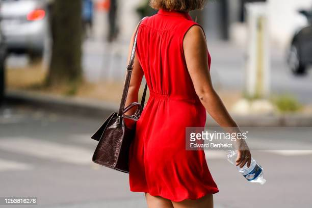 A passerby wears a red short sleeveless dress a brown leather crocodile pattern bag on June 28 2020 in Paris France