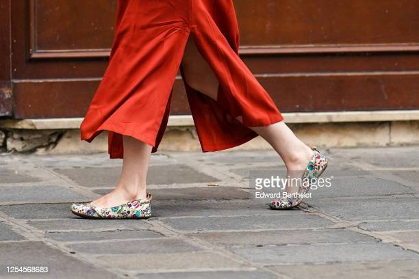 Passerby wears a red slit skirt, flat shoes with colored floral prints, on July 04, 2020 in Paris, France.