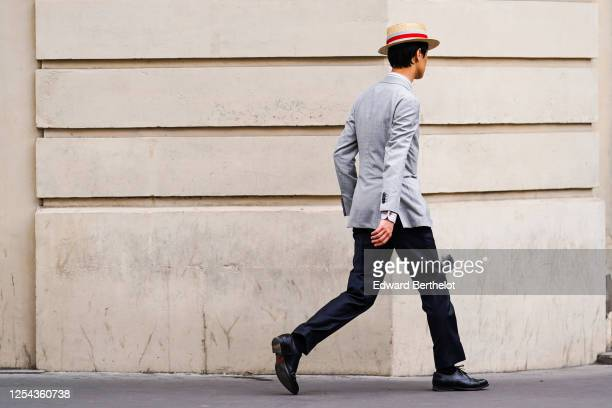 Passerby wears a straw hat, a gray blazer jacket, black suit pants, black leather shoes, on July 04, 2020 in Paris, France.
