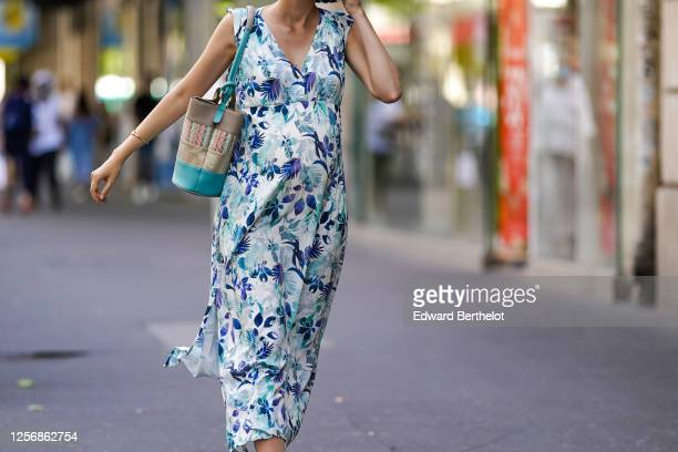 Passerby wears a v-neck blue and white floral print dress, a bag, on July 09, 2020 in Paris, France.