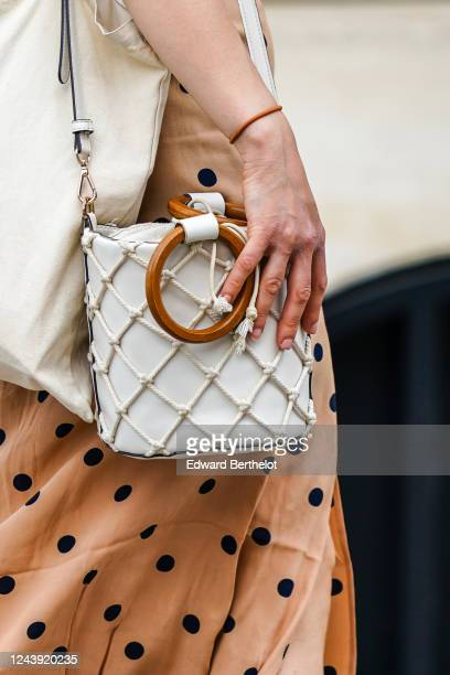 Passerby wears a white bag with a fishnet and circular wooden handles, a dress with polka dots, on June 03, 2020 in Paris, France.