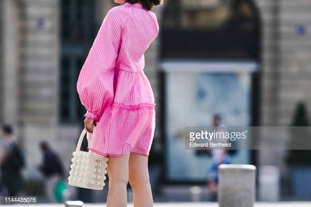 A passerby wears a white beaded rectangular bag a pink checkered dress on April 22 2019 in Paris France