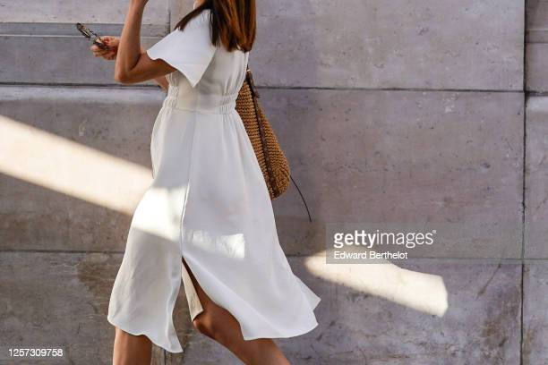Passerby wears a white dress, on July 08, 2020 in Paris, France.