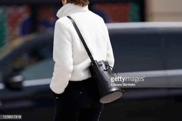 Passerby wears a white fluffy jacket, a black leather bag, in the streets of Paris, on May 11, 2020 in Paris, France.