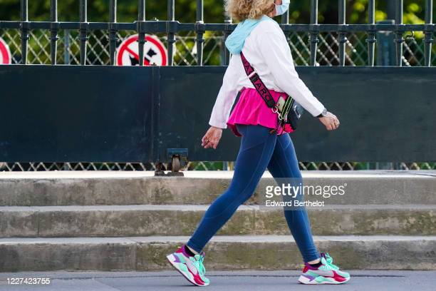 A passerby wears a white jacket a pale blue hood a face mask a pink long tshirt a Marc Jacobs bag strap blue leggings pastel colored sneakers shoes...