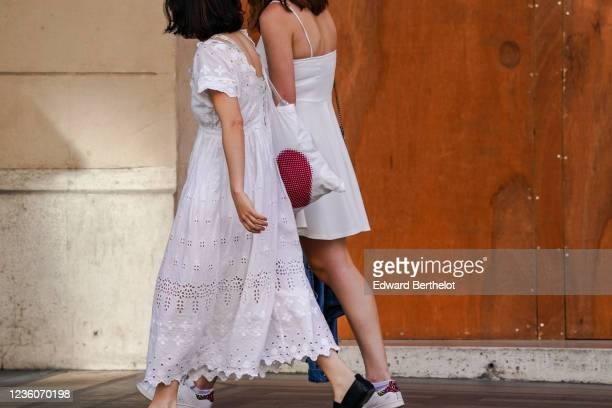 Passerby wears a white lace dress with several keyholes and embroidery, on May 30, 2020 in Paris, France.