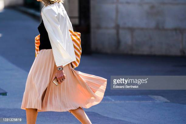 Passerby wears a white oversized blazer jacket, an orange striped tote bag, a black top, a pale pink pleated skirt, on May 28, 2020 in Paris, France.