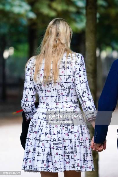 A passerby wears a white pleated Chanel tweed dress with shoulder pads on June 28 2020 in Paris France
