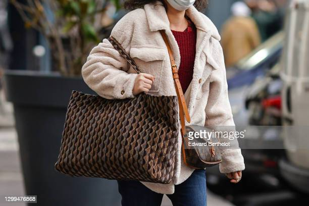 Passerby wears a white protective face mask, a white fluffy coat, a brown leather monogram printed Vuitton bag, a brown tote bag with printed...
