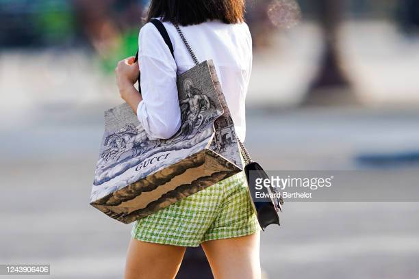 A passerby wears a white shirt a Gucci large tote bag green checked shorts on June 03 2020 in Paris France