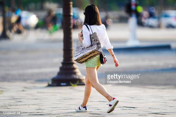 A passerby wears a white shirt a Gucci large tote bag green checked shorts Gucci sneakers on June 03 2020 in Paris France