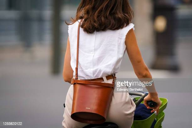 A passerby wears a white sleeveless top a brown leather cylindershaped Sezane bag beige pants a belt rides a bicycle on June 28 2020 in Paris France