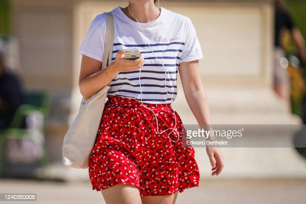 Passerby wears a white striped t-shirt, a red short floral print skirt, a tote bag, on May 31, 2020 in Paris, France.