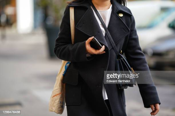 Passerby wears a white top, a black wool long winter coat, a leather bag, a tote bag, on January 28, 2021 in Paris, France.