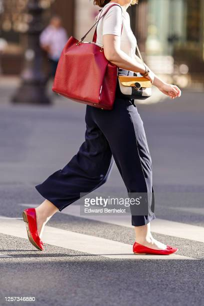 Passerby wears a white top, a red leather bag, large cropped pants, red flat shoes, on July 08, 2020 in Paris, France.