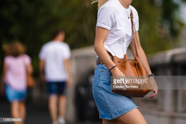 A passerby wears a white tshirt a brown Lancaster leather bag a blue denim skirt on July 25 2020 in Paris France