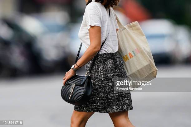 A passerby wears a white tshirt a Sezane Demain tote bag a black and white short skirt a Chloe black leather quilted bag a watch on June 03 2020 in...
