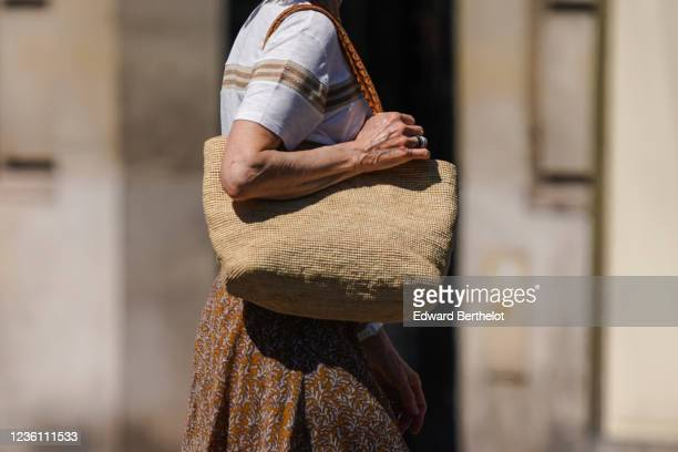 A passerby wears a white tshirt with a brown printed stripe a beige bag a flowing floral print skirt on May 30 2020 in Paris France