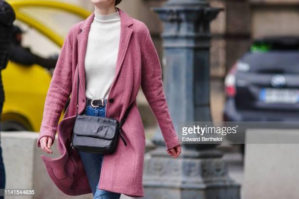 Passerby wears a white turtleneck top, a pink wool coat, a black bag, a belt, blue jeans, on April 07, 2019 in Paris, France.