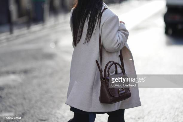 Passerby wears a white wool coat, a brown leather bag, on January 28, 2021 in Paris, France.
