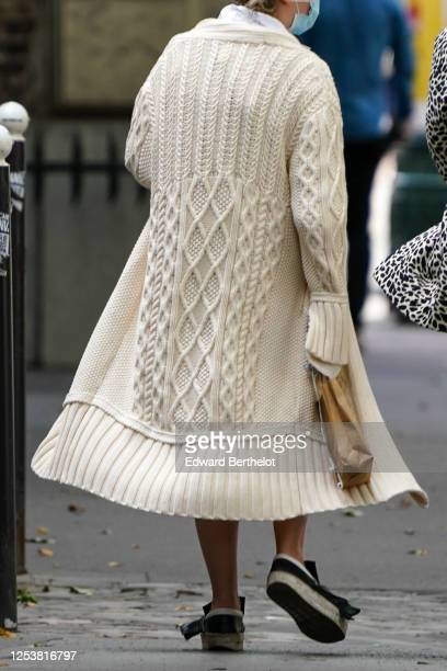 A passerby wears a white wool long knitted vest a blue protective face mask on June 28 2020 in Paris France