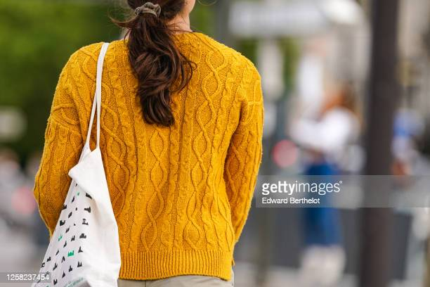 Passerby wears a yellow/orange wool knitted pullover, a tote bag, on July 25, 2020 in Paris, France.