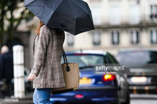A passerby wears an umbrella a checked blazer jacket a large beige bag denim blue jeans in Paris on May 18 2019 in Paris France