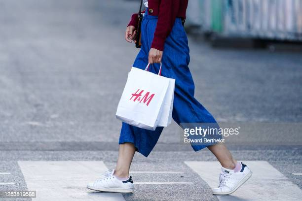 A passerby wears blue cropped pants Adidas Stan Smith sneakers shoes holds an HM / HM white paper shopping bag on June 28 2020 in Paris France
