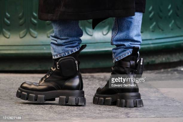 Passerby wears blue denim jeans and black leather Prada boots with pockets, in the streets of Paris, on March 15, 2020 in Paris, France.