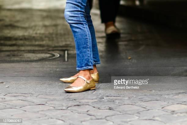 Passerby wears blue denim jeans, golden flat shoes, on September 03, 2020 in Paris, France.