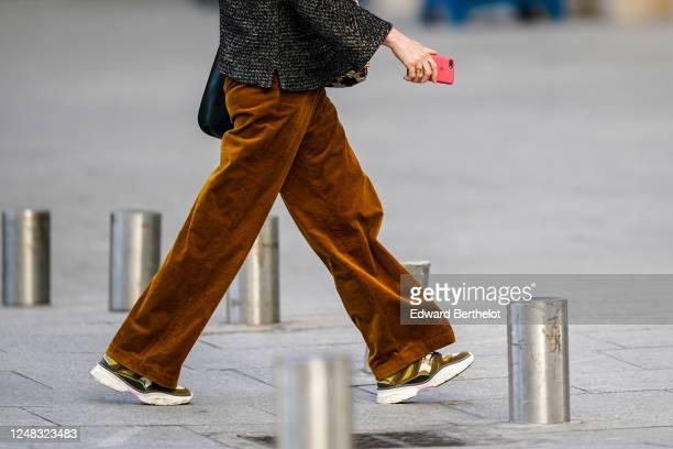 Passerby wears brown corduroy flared pants, sneakers shoes, on June 08, 2020 in Paris, France.