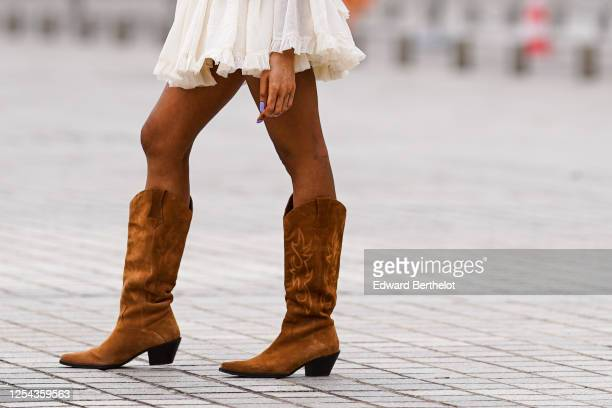 Passerby wears brown suede high cow-boy pointy boots, on July 04, 2020 in Paris, France.