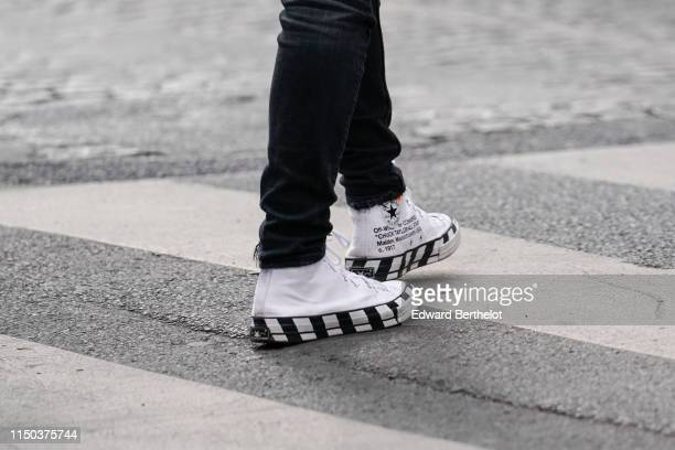 A passerby wears Converse x OffWhite black and white striped sneakers shoes in Paris on May 18 2019 in Paris France