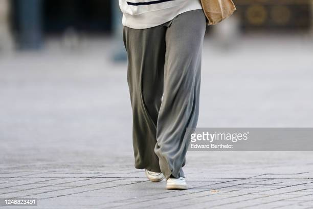 Passerby wears gray large flowing pants, white sneakers, on June 08, 2020 in Paris, France.