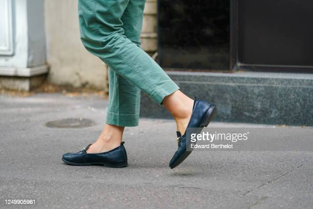 Passerby wears green cropped pants, flat shoes, on June 15, 2020 in Paris, France.