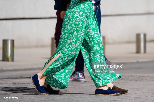 A passerby wears green floral print flowing pants blue flat shoes on June 28 2020 in Paris France