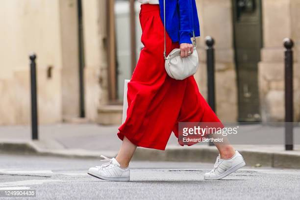 Passerby wears red flared large pants, a white bag, white sneakers, on June 15, 2020 in Paris, France.