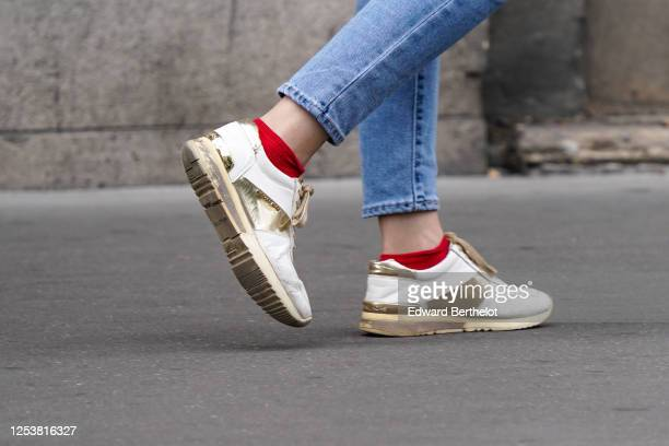A passerby wears white and golden Michael Kors sneakers shoes red socks on June 28 2020 in Paris France
