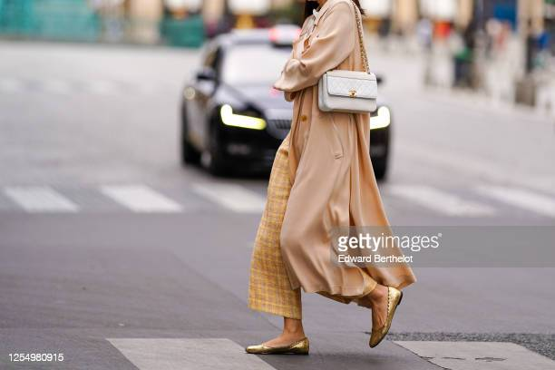 Passerby wears yellow checked wool knitted pants, golden flat ballerina shoes, a white Chanel bag, a salmon-pink flowing long coat, on July 04, 2020...