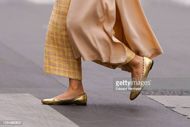 Passerby wears yellow checked wool knitter pants, golden flat ballerina shoes, on July 04, 2020 in Paris, France.
