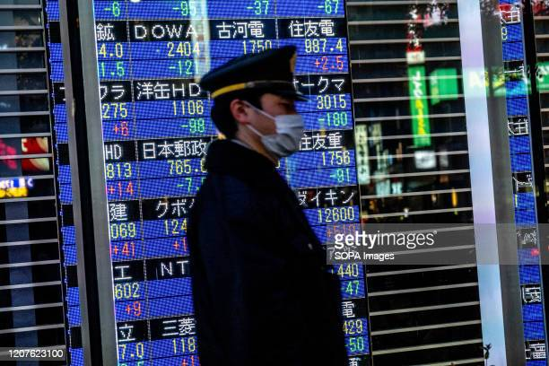 A passerby with a face mask walks past a stock board in Tokyo's Nihonbashi district showing the Nikkei average index falling on the Tokyo Stock...