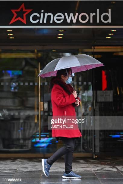 A passerby wrapped up against the rain walks past a cineworld cinema in Leicester Square in central London on October 4 2020 Cineworld is set to...