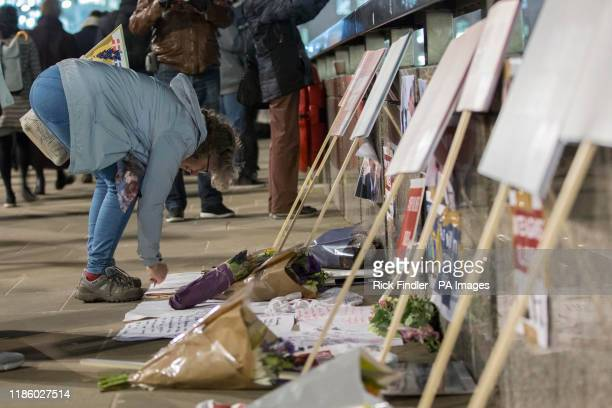 A passerby writes a message next to tributes to Cambridge University graduates Jack Merritt and Saskia Jones on London Bridge who were both stabbed...